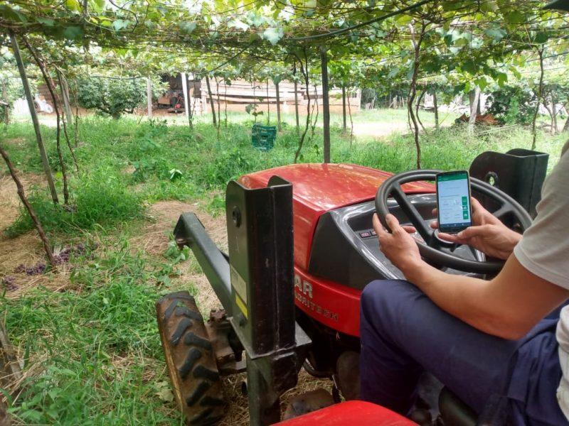 produtor com trator e celular